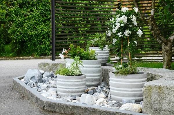 Cement Barrel Plant And Flower Pots Inside A Large Rock Garden